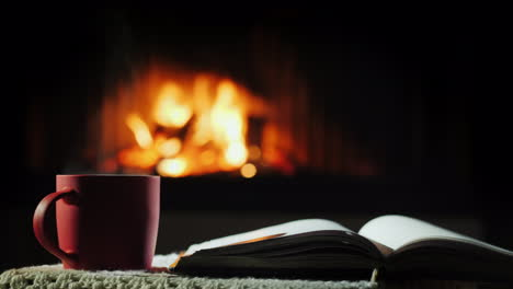 An-Open-Book-And-A-Cup-Of-Hot-Tea-On-The-Background-Of-The-Fireplace-Where-The-Fire-Is-Burning