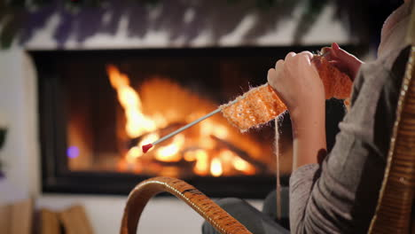 Rest-On-A-Winter-Evening---A-Woman-Knits-While-Sitting-By-A-Fireplace-Decorated-For-Christmas-4k-Vid
