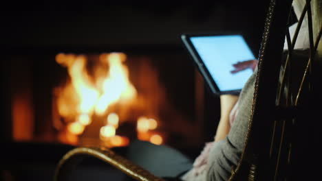 A-Woman-Uses-A-Tablet-While-Sitting-In-A-Rocking-Chair-By-The-Fireplace-At-Home