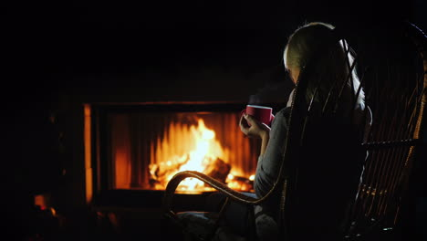 Middle-Aged-Woman-Drinks-Hot-Tea-By-The-Fireplace-Winter-Escape-Concept