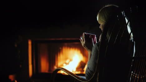 Drinking-Hot-Tea-By-The-Fire-The-Woman-Resting-At-Home-Near-The-Fireplace-Where-The-Fire-Is-Burning