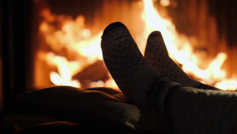 Legs-In-Socks-Are-Heated-By-The-Fireplace-In-Winter-Evening