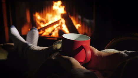 Woman-With-A-Red-Cup-Of-Tea-Is-Relaxing-By-The-Fireplace