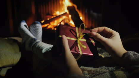 Woman-Holds-A-Box-With-A-Gift-In-Her-Hands-Sits-Near-The-Fireplace