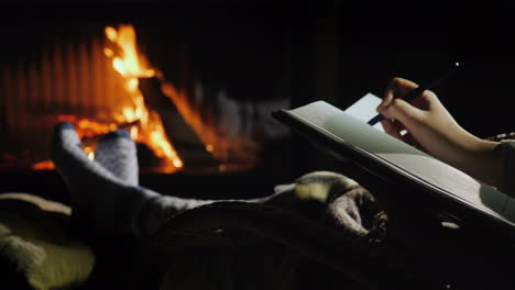 Writing-In-A-Notebook-While-Sitting-By-The-Fireplace-Plans-For-The-New-Year-Start-With-A-Blank-Sheet