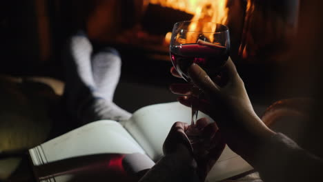 Woman-Sitting-By-The-Fireplace-With-A-Notebook-And-A-Glass-Of-Red-Wine