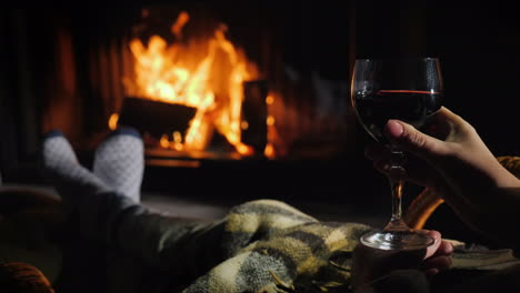 Bask-Under-A-Blanket-By-The-Fireplace-With-A-Glass-Of-Wine-In-His-Hand-Winter-Escape-Concept