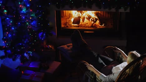 Woman-Resting-By-The-Fireplace-On-Christmas-Eve-Top-View