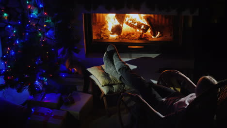 Evening-By-The-Fireplace---A-Young-Woman-Resting-In-A-Rocking-Chair-Looking-At-The-Fire-In-The-Firep