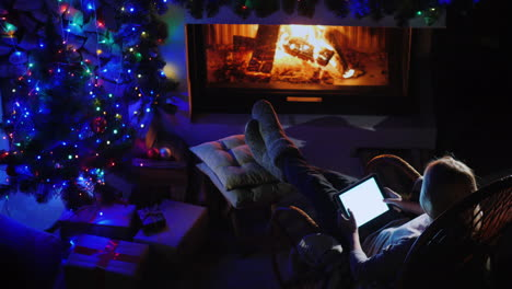 Young-Woman-Resting-By-The-Fireplace-Using-A-Tablet
