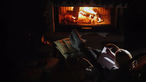 Woman-Writes-In-A-Notebook-While-Sitting-By-The-Fireplace