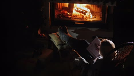 Young-Woman-Reads-A-Book-While-Sitting-By-The-Fireplace