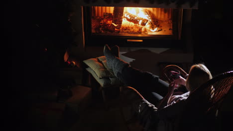 Woman-With-A-Glass-Of-Wine-Is-Relaxing-By-The-Fireplace-Top-View