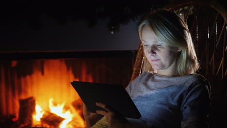 A-Young-Woman-Uses-A-Digital-Tablet-In-A-Cozy-House-Near-The-Fireplace-Where-The-Flame-Is-Burning