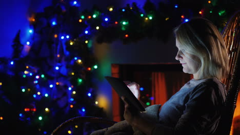 Woman-Uses-A-Tablet-Against-The-Background-Of-A-Fireplace-And-Festive-Garlands