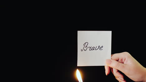 Man-Burns-A-Paper-With-The-Inscription-Brave
