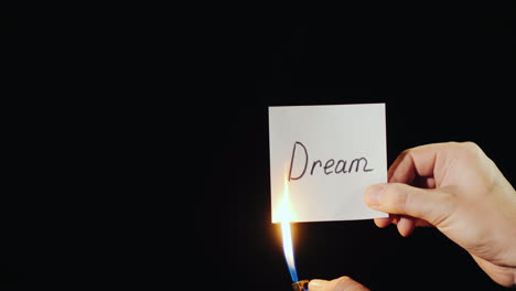 Hand-Holds-Burning-Paper-With-Inscription-Dream