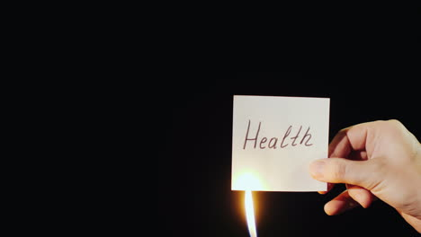 Hand-Holds-Burning-Paper-With-Inscription-Health