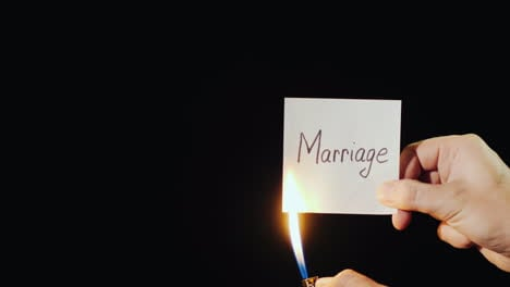 Hand-Holds-Burning-Paper-With-Inscription-Marriage