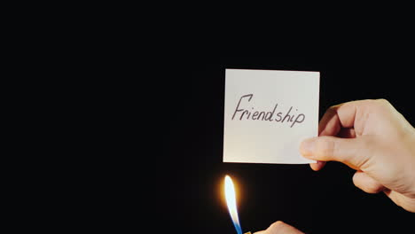 Hand-Holds-Burning-Paper-With-Inscription-Friendship
