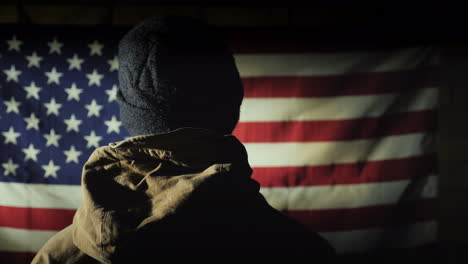 The-Silhouette-Of-A-Man----He-Looks-At-The-American-Flag-On-The-Brick-Wall-The-View-From-Behind