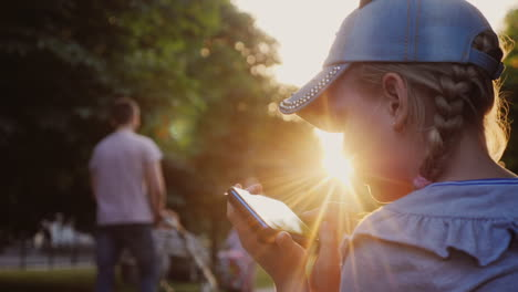 A-Child-Plays-On-A-Smartphone-Sits-In-A-Park-On-A-Bench