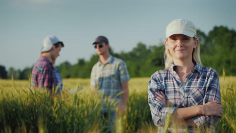 Portrait-Of-A-Female-Farmer-Against-The-Background-Of-Wheat-Fields-And-Other-Farmers
