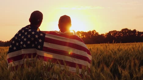 Two-Men-With-The-Flag-Of-America-On-Their-Shoulders-Look-At-The-Sunrise-Above-A-Wheat-Field