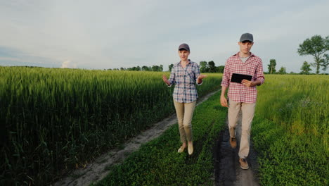 A-Couple-Of-Young-Farmers-Walk-Along-A-Country-Road-Between-Wheat-Fields