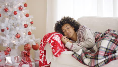 Woman-sleeping-on-couch-beside-Christmas-tree