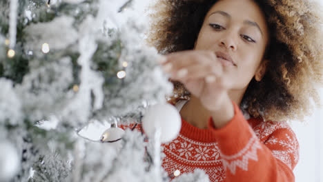 Pretty-young-woman-decorating-a-Christmas-tree