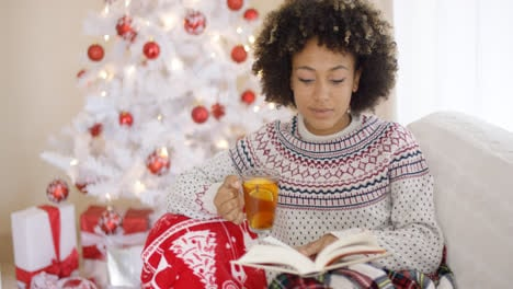 Woman-reading-a-book-in-front-of-Christmas-tree