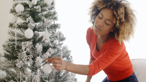Pretty-young-woman-decorating-an-Xmas-tree