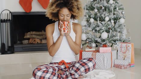 Blissful-young-woman-drinking-coffee-at-Christmas