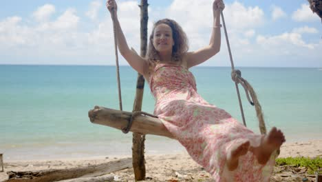 Cheerful-woman-riding-self-made-swing-on-beach