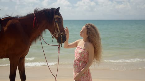 Long-haired-woman-stroking-brown-horse-in-face-on-seaside