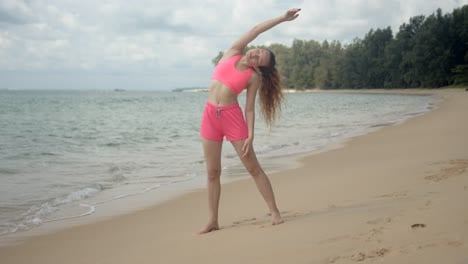 Active-woman-in-pink-swimsuit-making-workout-on-beach
