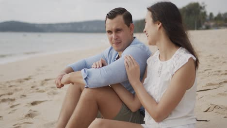 Couple-on-vacation-sitting-on-sand-of-seashore-and-smiling