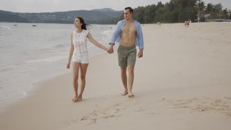 Male-and-female-lovers-going-on-seashore-while-enjoying-in-views