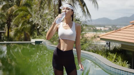 Slim-sportswoman-drinking-water-near-swimming-pool