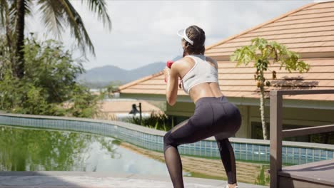 Strong-female-squatting-near-swimming-pool