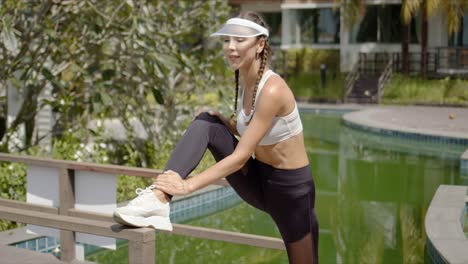 Pleased-sportswoman-stretching-leg-on-path-near-swimming-pool