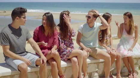 Group-of-young-students-relaxing-at-the-seaside