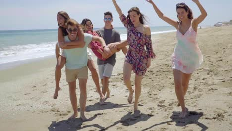 Group-of-young-friends-frolicking-on-a-beach