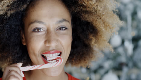 Young-woman-biting-a-festive-candy-cane