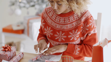 Young-woman-carefully-wrapping-a-Christmas-gift