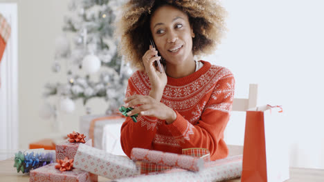 Woman-chatting-on-a-mobile-as-she-wraps-gifts