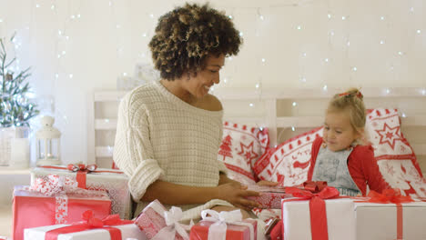 Mother-showing-female-child-Christmas-gifts