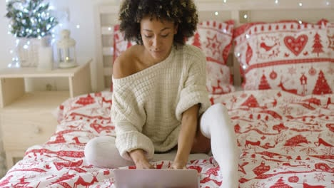 Woman-in-oversized-sweater-on-bed-using-laptop