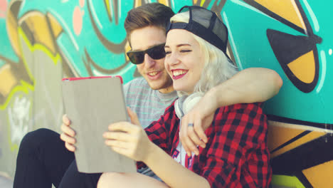 Young-hipster-urban-couple-relaxing-on-a-sidewalk